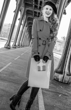 shopper: Full length portrait of happy elegant woman in red trench coat on Pont de Bir-Hakeim bridge in Paris holding shopping bag and Christmas present box