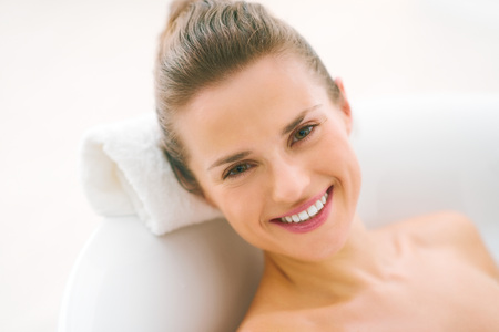 Portrait of smiling young woman laying in bathtub Stock Photo