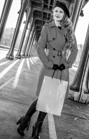 Full length portrait of happy young woman in red trench coat on Pont de Bir-Hakeim bridge in Paris with shopping bag  looking into the distance