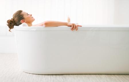 Relaxed giovane donna che propone in vasca da bagno Archivio Fotografico - 80681502