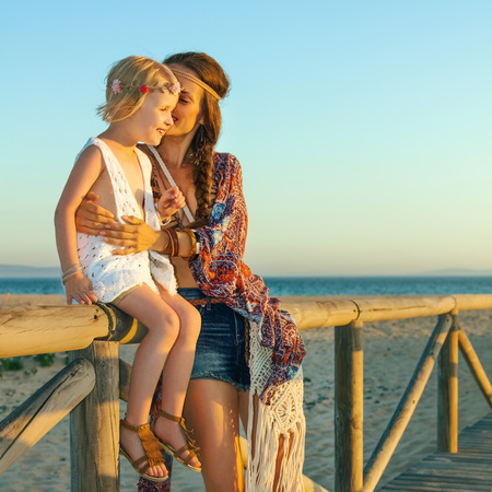 Bohemian vibe vacation. Full length portrait of happy hipster mother and daughter outdoors in the summer evening having fun time