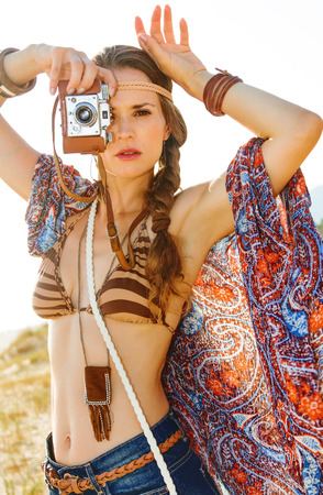 trendy hippie in jeans shorts and cape outdoors in the summer evening with retro photo camera