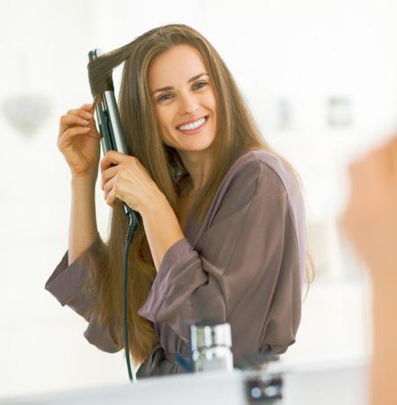 스트레이트 너와 머리카락을 컬링 웃는 여자