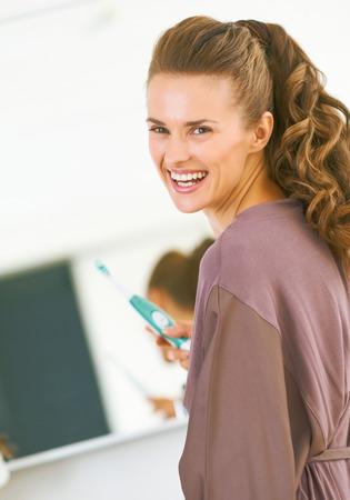 浴室で歯ブラシを持つ幸せな若い女性 写真素材
