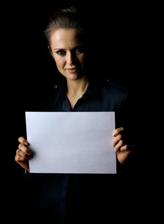 ?oming out into the light. Portrait of woman in the dark dress isolated on black background showing blank paper sheet