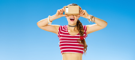 Perfect summer. smiling active woman on the seacoast wearing cardboard VR gear 版權商用圖片