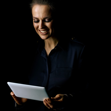 ?oming out into the light. Portrait of smiling woman in the dark dress isolated on black using tablet PC Stock Photo