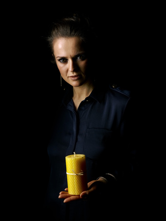 Ð¡oming out into the light. Portrait of woman in the dark dress isolated on black background showing a candle