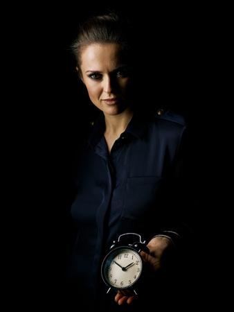 �Het licht in. Portret van vrouw in de donkere die kleding op zwarte wordt geïsoleerd die wekker tonen
