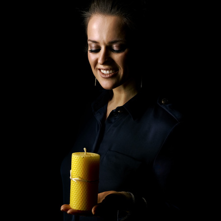 Сoming out into the light. smiling woman in the dark dress isolated on black background looking at a candle