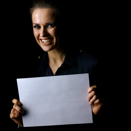 Ð¡oming out into the light. Portrait of smiling woman in the dark dress isolated on black background showing blank paper sheet