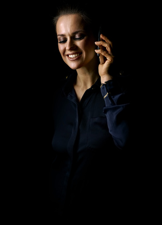 Ð¡oming out into the light. Portrait of happy woman in the dark dress isolated on black background using a cell phone Stock Photo