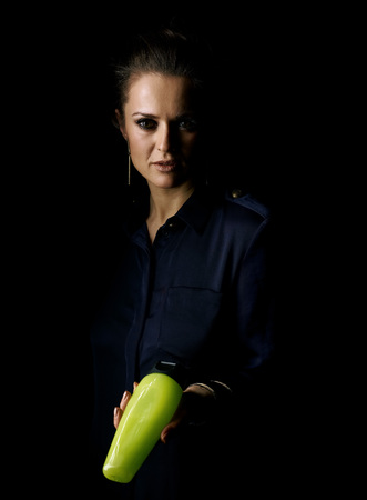 Сoming out into the light. Portrait of woman in the dark dress isolated on black showing a bottle of cosmetics