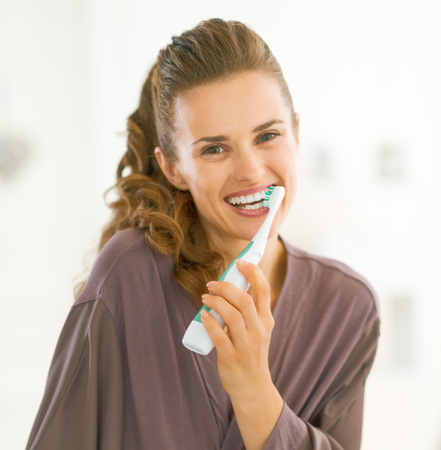 Happy young woman brushing teeth in bathroom Фото со стока