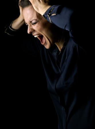 光に Сoming。黒の背景に分離された暗いドレスの怒っている女性 写真素材