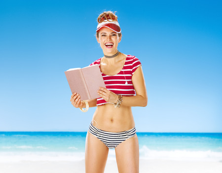Perfect summer. smiling fit woman in red sun visor on the beach with book