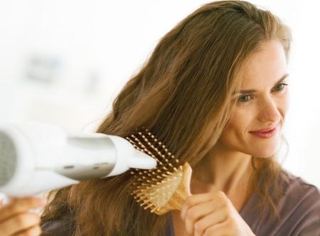 幸せな女を磨くし、浴室で髪を乾燥打撃
