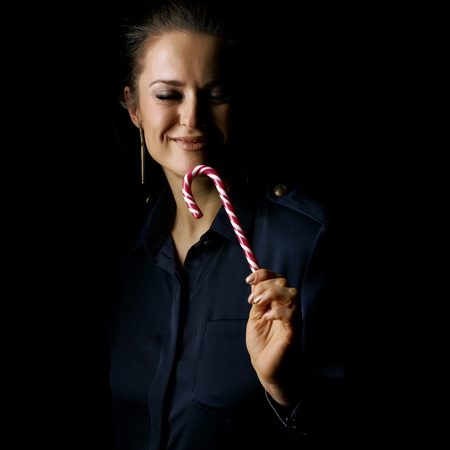 Ð¡oming out into the light. Portrait of smiling woman in the dark dress isolated on black enjoying christmas candy cane Stock Photo