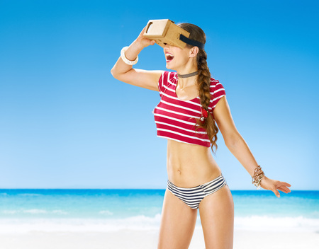 futuristic: Perfect summer. happy active woman on the seacoast in cardboard virtual reality gear