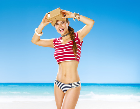 futuristic: Perfect summer. Portrait of smiling active woman on the seashore with cardboard VR glasses