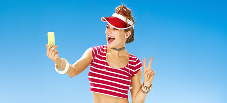 Perfect summer. smiling young woman in red sun visor on the beach with cellphone taking selfie and showing victory gesture