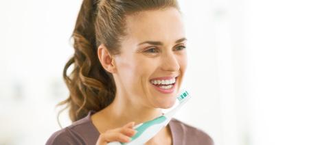 욕실에서 치아를 칫솔질하는 행복 한 젊은 여자 스톡 콘텐츠