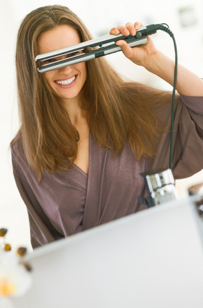 Happy young woman looking through hair straightener in bathroom Stock Photo