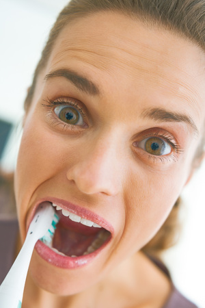 Funny portrait of young woman intensively brushing teeth Stok Fotoğraf