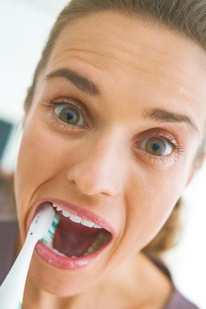 Grappig portret van jonge vrouw intensief poetsen tanden