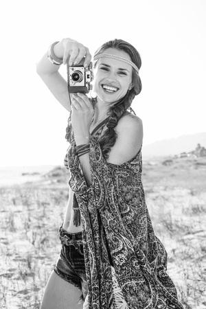 Vacaciones de ambiente bohemio. Retrato de feliz con estilo boho chica en jeans cortos y capa al aire libre en la noche de verano con cámara de fotos retro Foto de archivo - 81175827