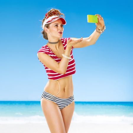 Perfect summer. smiling fit woman in red sun visor on the beach with cellphone taking selfie and blowing air kiss