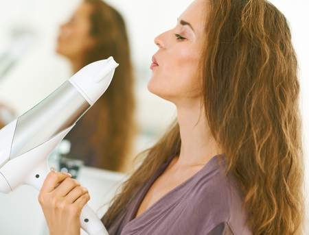 Happy young woman blowing on blow dryer Stock Photo