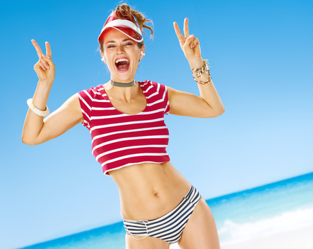 Perfect summer. smiling healthy woman in red sun visor on the seashore with headphones listening to the music and showing victory gesture