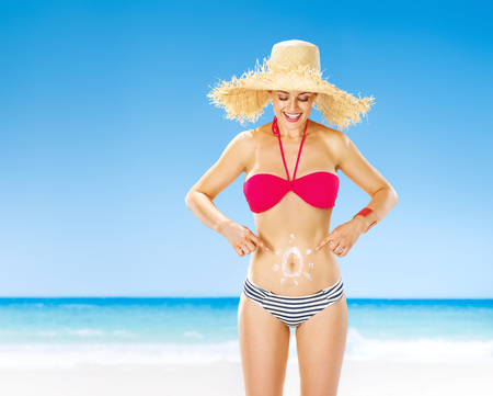 Perfect summer. happy fit woman on the seashore pointing on sun drawn by spf creme on the stomach