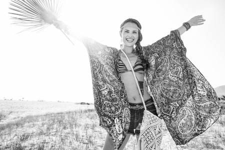 ethno: Bohemian vibe vacation. cheerful fashion bohemian chic in jeans shorts and cape outdoors in the summer evening with big green tropical leaf rejoicing Stock Photo