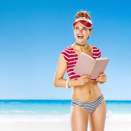 완벽한 여름. 붉은 태양 바이 컬러 행복 활성 여자 복사 공간을 찾고 책을 함께 해안에