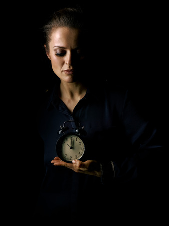 ?oming out into the light. Portrait of woman in the dark dress isolated on black background showing alarm clock