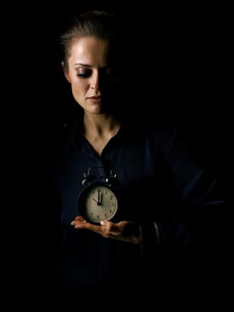 Om in het licht uit te gaan. Portret van vrouw in de donkere jurk geïsoleerd op zwarte achtergrond wekker Stockfoto