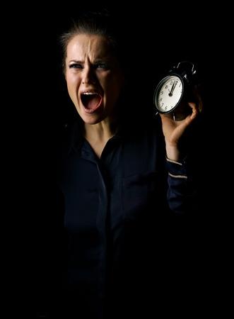 ? Wegwezen in het licht. Portret van gestresste vrouw in de donkere die kleding op zwarte achtergrond met wekker wordt geïsoleerd Stockfoto