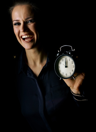 Ð¡oming out into the light. smiling woman in the dark dress isolated on black showing alarm clock Stock Photo