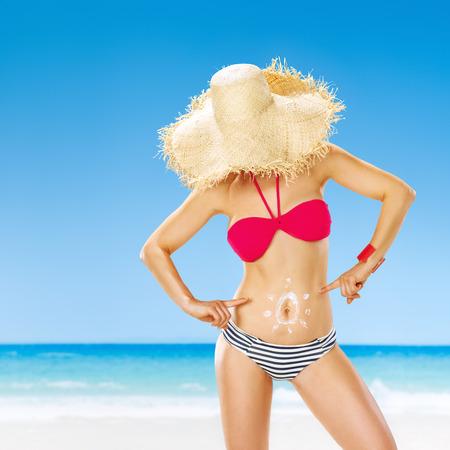 Verano perfecto mujer joven se esconde detrás de sombrero de paja en la orilla del mar apuntando en sol dibujado por spf crema en el estómago Foto de archivo - 81177007