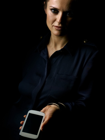 ?oming out into the light. Portrait of woman in the dark dress isolated on black showing smartphone