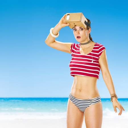futuristic: Perfect summer. surprised healthy woman on the beach in cardboard virtual reality gear