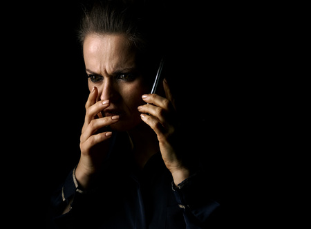 ?oming out into the light. Portrait of stressed woman in the dark dress isolated on black background speaking on a smartphone Foto de archivo