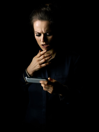 ?oming out into the light. Portrait of stressed woman in the dark dress isolated on black reading sms