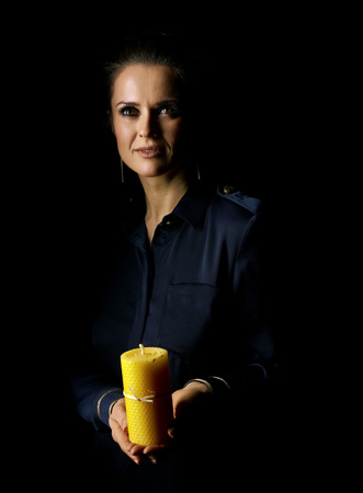 Сoming out into the light. Portrait of woman in the dark dress isolated on black background showing a candle and looking up