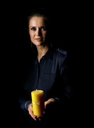 빛을 향해 밖으로. 촛불을 게재 하 고 찾고 검은 배경에 고립 된 어두운 드레스에서 여자의 초상화 스톡 콘텐츠