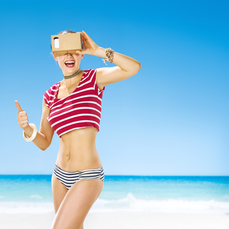 futuristic: Perfect summer. Portrait of smiling active woman on the seacoast showing thumbs up and wearing cardboard virtual reality gear