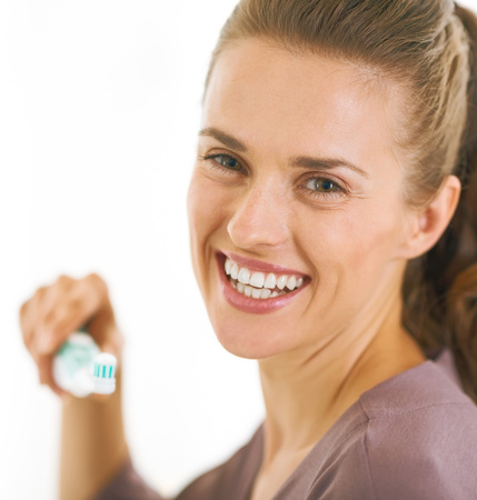 Portrait of smiling young woman holding toothbrush with toothpaste