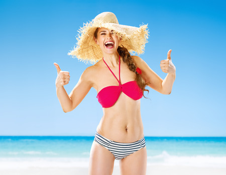 Perfect summer. Portrait of smiling healthy woman on the seacoast showing thumbs up